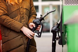 Close-up of hands of woman at self-service gas station, hold fuel nozzle and refuel the car with petrol, diesel, gas. Close up of filling auto with gasoline or benzine. Self service gas pump