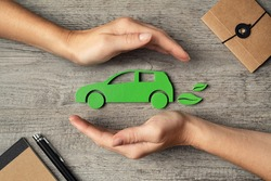 Close up of hands of woman protecting icon of green eco-friendly car over wooden table. Top view of woman hands protecting electric car with care, mobility. Car insurance and green automotive concept.