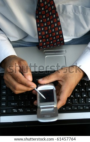 close up of hands of young executive using high end mobile phone and laptop - stock photo