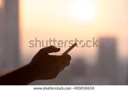Close-up of hands of young man holding mobile phone, using smartphone app, scrolling. silhouette against sunny street view #400058650