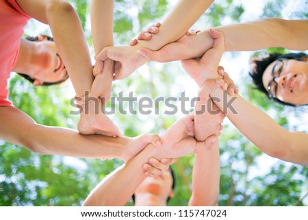 Close-up of hands of young people joined in a circle