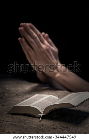 Close up of hands of young woman praying near the Bible. She is clapping her arms together #344447549
