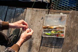 Close up of hands setting lure as bait. He is working on raft while floating over river. Box with hooks is in background.