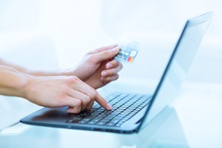 Close-up of hands shopping/paying online using laptop and credit card.