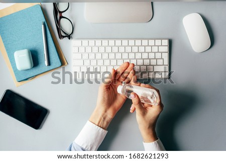 Close-up of hands using antiseptic gel to disinfect hands over a work desk in an office. Preventive measures during the period of epidemic and social exclusion.