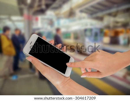 Close up of hands using cell phone at a station platform, train background #304617209
