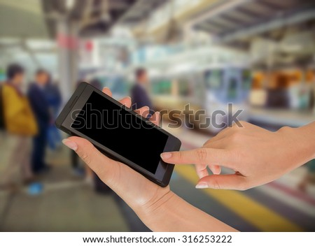 Close up of hands using cell phone at a station platform, train background #316253222