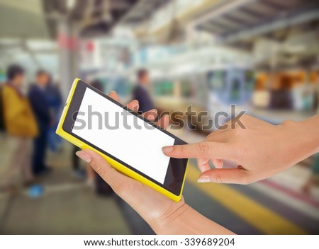 Close up of hands using cell phone at a station platform, train background #339689204