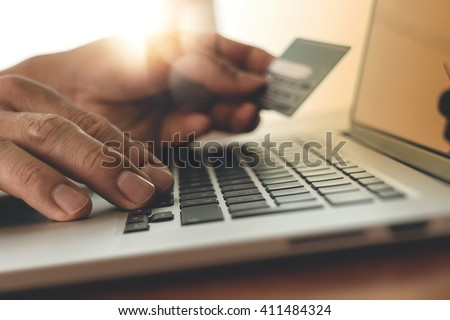 close up of hands using laptop and holding credit card with social media diagram as Online shopping concept