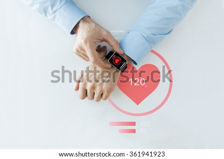 close up of hands with heart icon on smart watch