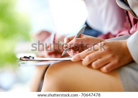 Close-up of hands with pens and legs in line outdoor