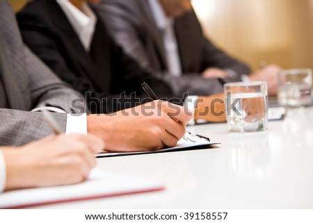 Close-up of hands with pens making notes during conference