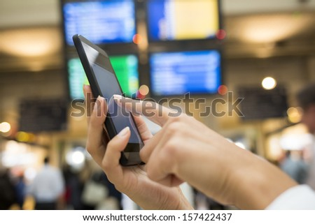 Close up of hands woman using her cell phone in station, background time display panels