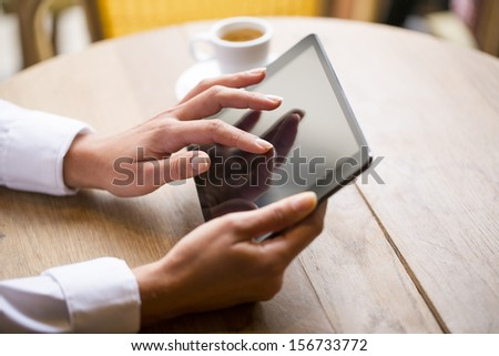Close up of hands woman using her tablet pc in restaurant cafe