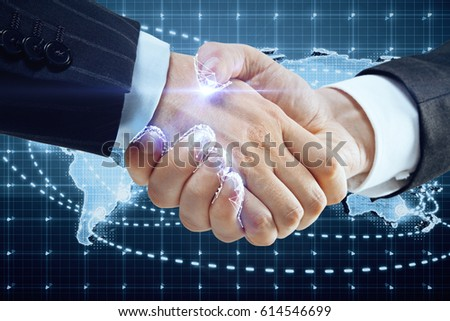 Close up of handshake with digital pattern and map. Global partnership concept #614546699