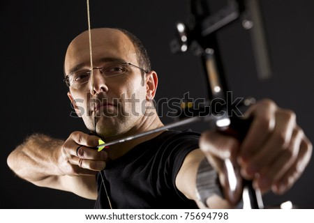 Close up of handsome archer in black on black background aiming with bow and arrow, side view with focus on eyes.