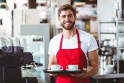 Close up of handsome barista holding two cups of coffee in the cafe
