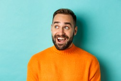 Close-up of handsome caucasian man smiling, looking left with surprised face, staring at logo, wearing orange sweater, standing against turquoise background
