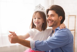 Close up of handsome cheerful father dancing with his princess daughter indoor, happy to be father, copy space