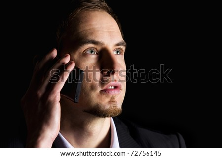 Close up of handsome young businessman in dark suit  talking on mobile-phone and looking up, low-key image isolated on black background.