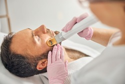 Close up of handsome young man with closed eyes having laser hair removal procedure in beauty salon