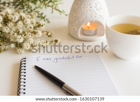 """Close up of handwritten text """"I am grateful for..."""" in foreground with notebook, pen,  cup of tea, flowers and oil burner in soft focus (deliberate angle)"""