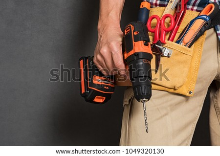 Close up of handyman holding a drill machine with tool belt around waist. Detail of artisan hand holding electric drill isolated over grey background. Hand of bricklayer holding carpentry accessories.