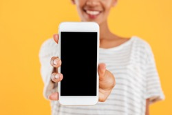 Close up of happy african lady showing smartphone with blank screen and smiling isolated