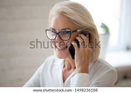 Close up of happy aged businesswoman in glasses talk on smartphone consulting client online, smiling senior woman wearing spectacles speak on cellphone, use wireless connection. Technology concept