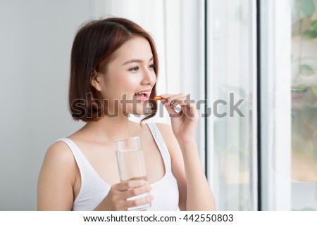 Close Up Of Happy Asian Woman Taking Pill With  Omega-3 And Holding A Glass Of Fresh Water In Morning. Vitamin D, E, A Fish Oil Capsules. Nutrition. Healthy Eating, Lifestyle.