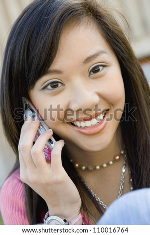 Close up of happy Asian woman using cell phone
