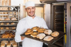 Close up of happy baker showing tray of fresh bread in the kitchen of the bakery