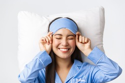 Close-up of happy beautiful asian girl in sleeping mask and blue pajamas lying in bed, smiling upbeat, having perfect mood as going bed and getting ready sleep, standing white background