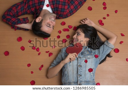 Close-up Of Happy Couple Lying On Floor Holding Heart  #1286985505