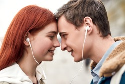 Close up of happy couple of teenagers listening to music using the same pair of earphones, looking at each other with love. Technology, romance concept. Side view. Horizontal shot