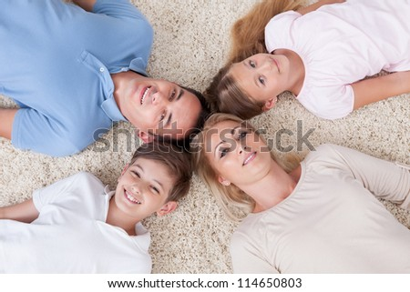 Close-up Of Happy Family Lying On Carpet Looking Up Heads Together At Home