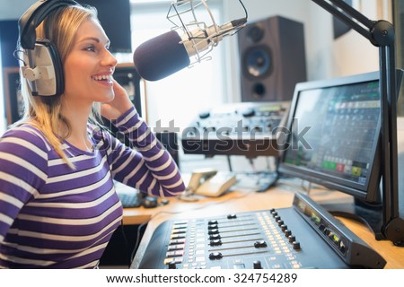 Close-up of happy female radio host broadcasting through microphone in studio #324754289