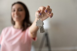 Close up of happy female renter tenant show keys buy purchase first own home or apartment, woman moving relocating to new dwelling, excited client settle in house, relocation, rental, realty concept