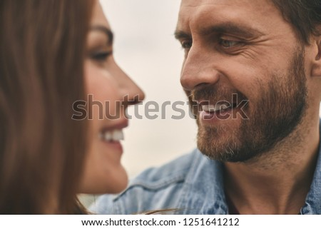 Close up of happy man is tenderly looking at pretty smiling woman while standing outdoor #1251641212
