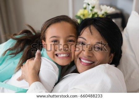 Close up of happy mature woman embracing girl on bed at home #660488233