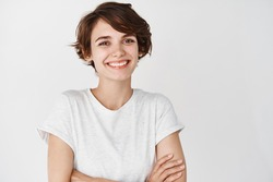 Close-up of happy professional girl cross arms on chest, smiling at camera, white background. Copy space