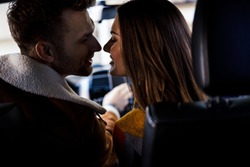 Close up of happy romantic people smiling and nearly kissing in the car