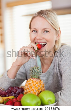 Close up of happy smiling woman having a strawberry