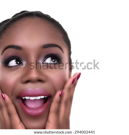 Close up of happy surprised excited black African American woman in make up and nail polish looking sideways at copy space