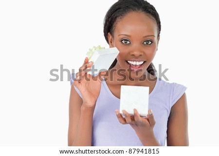 Close up of happy woman opening a present against a white background