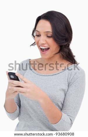 Close up of happy woman reading text message against a white background