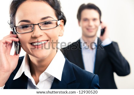 Close-up of happy woman speaking on the phone and looking  at camera