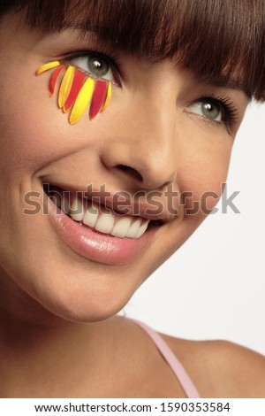 Close-up of happy woman with flower petals under eye