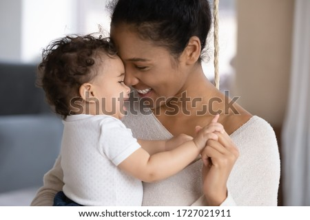 Close up of happy young african American mother hug cuddle little infant or toddler, loving smiling biracial mom embrace small baby child, enjoy tender family moment, motherhood, childcare concept
