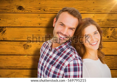 Close up of happy young couple standing back to back against yellow paint splashed surface #569795215